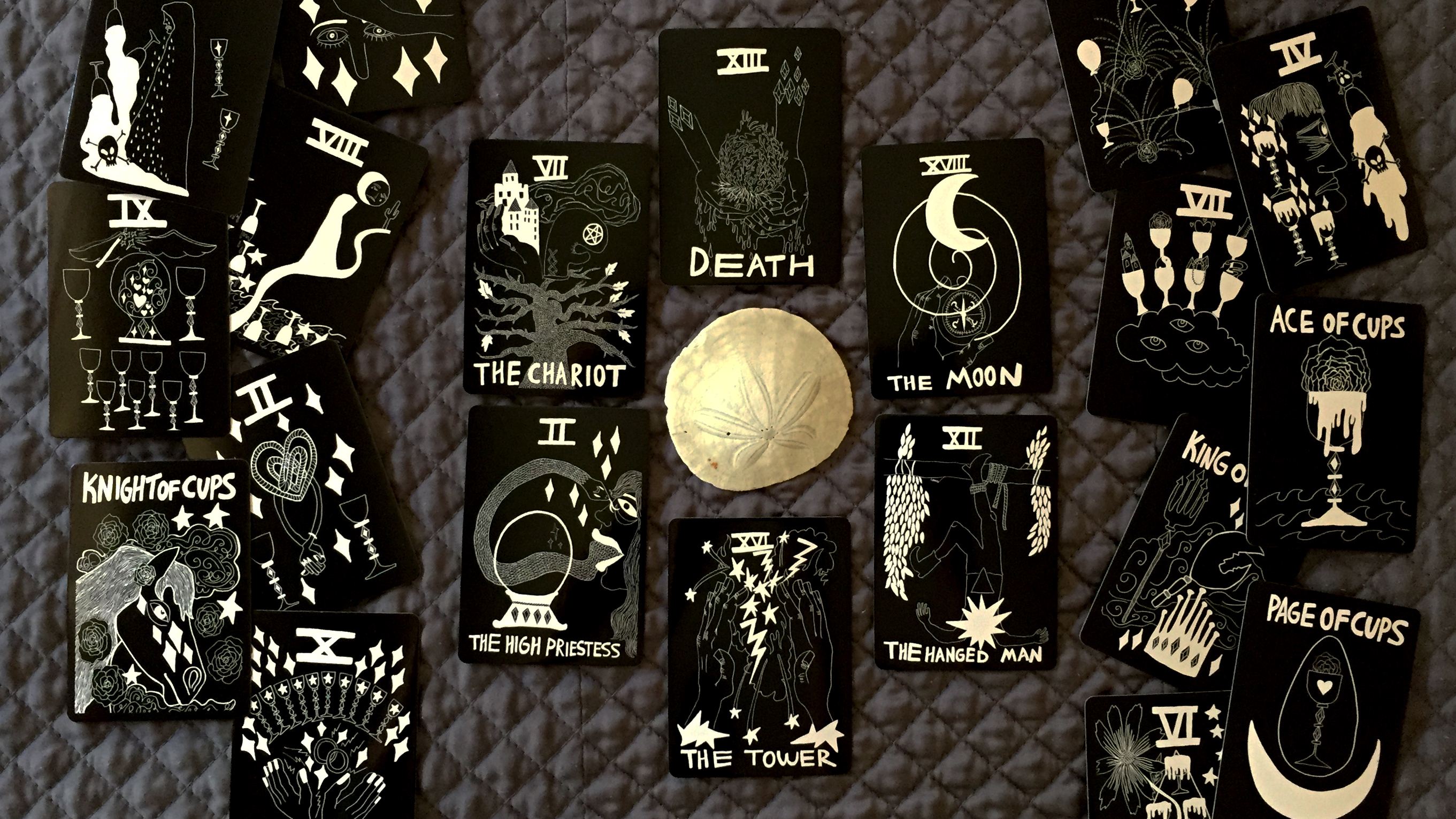 Water cards in tarot, with the Chariot, Death, Moon, Hanged Man, Tower, High Priestess, and all cards in the Cups suit arranged around a sand dollar.