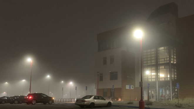 Heavy fog over streetlights in a parking lot with a building in the background