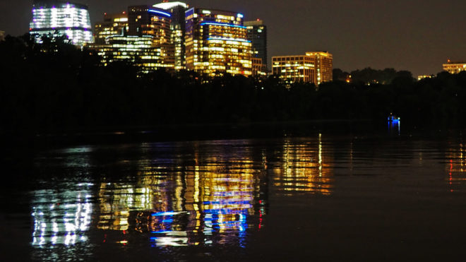 River water reflecting city lights at night