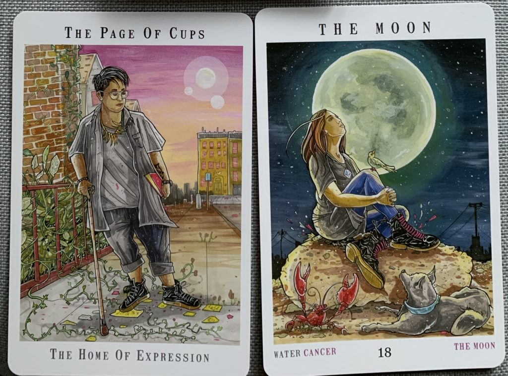 The Page of Cups and The Moon from Next World Tarot. The Page uses a cane and has paused to look at what may turn into found art on a city sidewalk; the Moon shows a woman on a rock with a bird perched on her knee, both observing the full moon as a dog and crayfish watch from the ground.